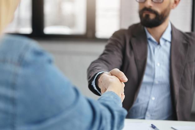 Succesvolle ondernemers schudden elkaar de hand na een ondertekend contract