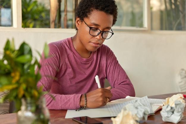 Succesvolle ontwerper met zwarte huid, jongensachtig kapsel, schrijft plan voor de week op blanco papier