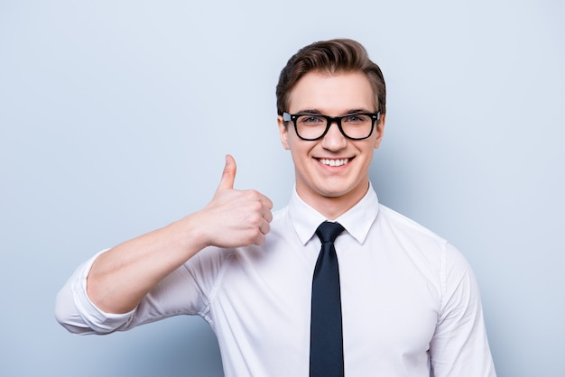 Succesvolle opgewonden jonge kerel in glazen en formele kleding staat geïsoleerd op een zuivere ruimte, duim omhoog teken, glimlachend
