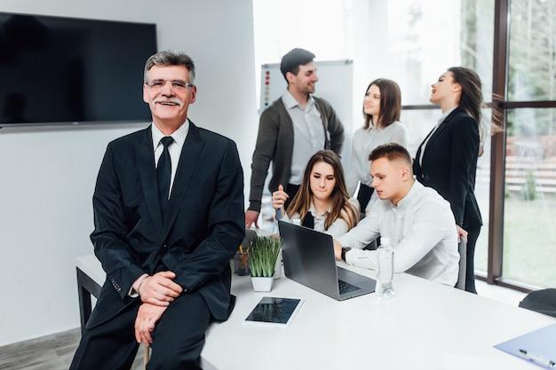 Succesvolle oudere zakenman met zijn team dat op modern kantoor werkt.