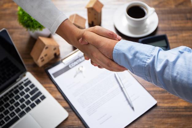 Succesvolle overeenkomst, landgoed, het concept van het huis het kopen contract, koper het schudden hand met bankheer na het ondertekenen van contract in bureau