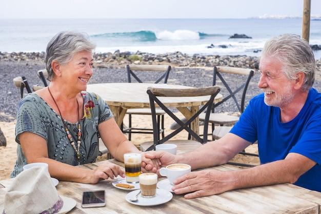 Succesvolle pensionering recreatie, zomervakantie concept. gepensioneerd volwassen koppel genieten van een mooie zonnige dag op het strand. gelukkig senior vrouw en man zitten aan de bar met houten tafels door de se