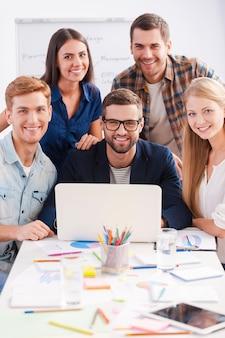 Succesvolle ploeg. groep creatieve zakenmensen in slimme vrijetijdskleding die samenwerken en glimlachen