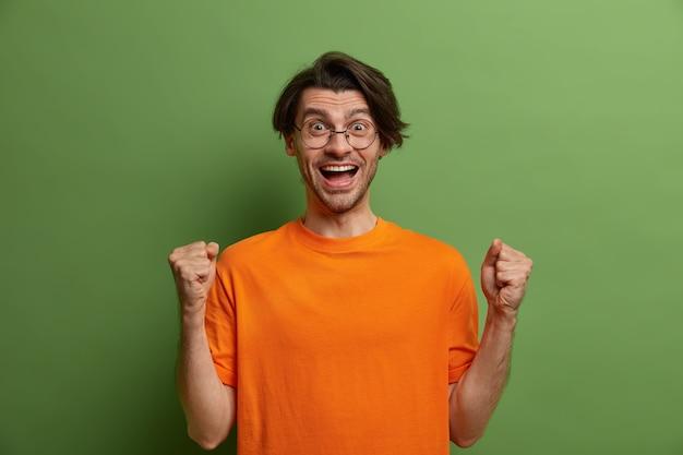 Succesvolle positieve vrolijke man balde vuisten en krijgt triomf, maakt hoera, verheugt zich over veel of goed nieuws, viert de overwinning, voelt zich als een echte kampioen, gekleed in heldere kleding