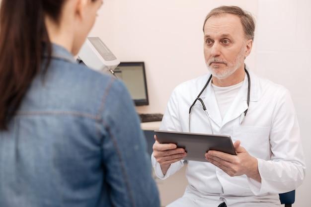Succesvolle privé-ervaren arts die met zijn patiënt praat en naar haar zorgen luistert terwijl hij een tablet in zijn handen houdt
