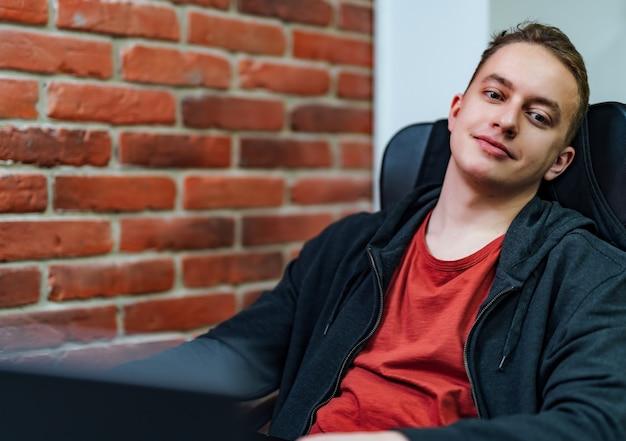 Succesvolle programmeur zittend in een comfortabele zwarte stoel en camera kijken in it-bedrijf. programming. afbeelding van hoge kwaliteit.
