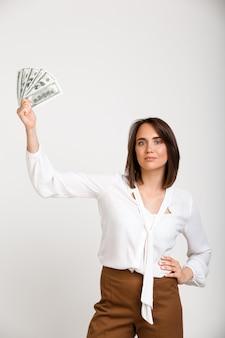 Succesvolle rijke maniervrouw die geld toont