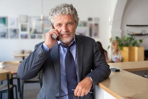 Succesvolle rijpe zakenman die op mobiele telefoon spreekt, zich bij co-working bevindt, op bureau leunt, camera a bekijkt