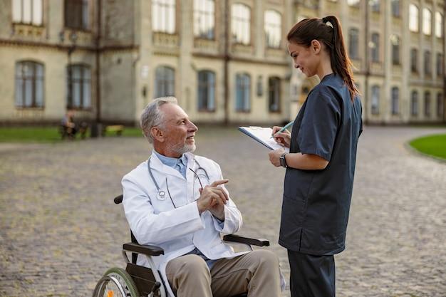 Succesvolle senior gehandicapte mannelijke arts in rolstoel met laboratoriumjas in gesprek met jonge verpleegster