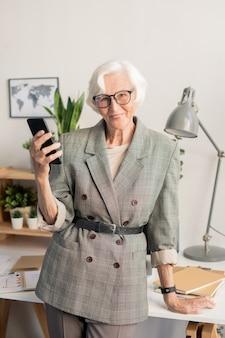 Succesvolle senior zakenvrouw met mobiele gadget op zoek naar jou terwijl leunend door bureau met werkende benodigdheden