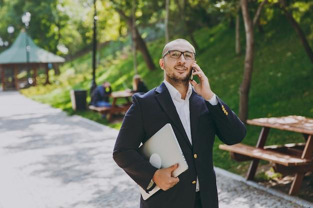 Succesvolle slimme zakenman in wit overhemd, klassiek pak, bril. man staan met laptop pc-computer, praten op mobiele telefoon in stadspark buiten op natuur achtergrond. mobiel kantoor, bedrijfsconcept.