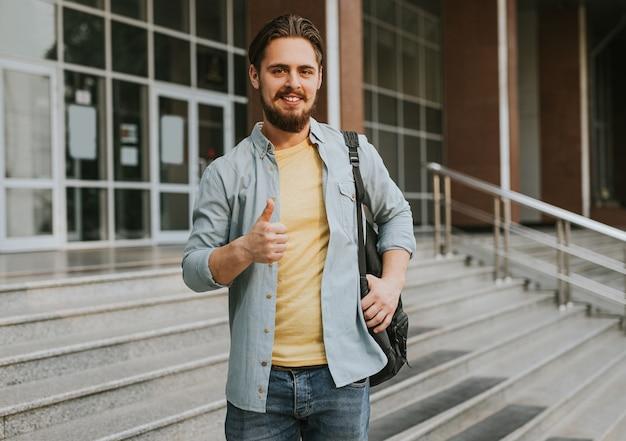 Succesvolle student die duim toont