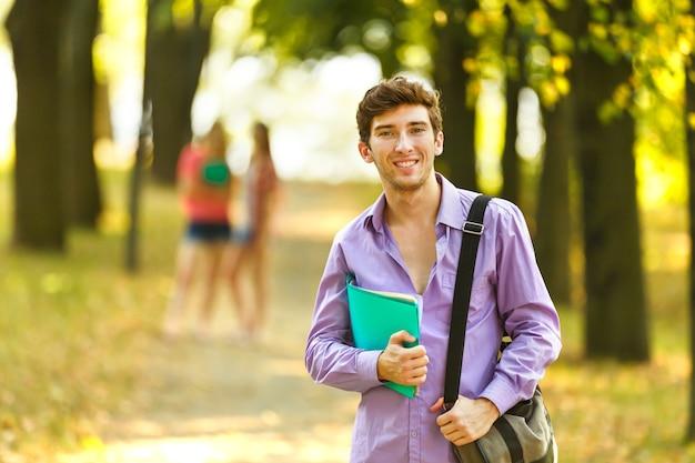 Succesvolle student met boeken in het park op een zonnige dag.