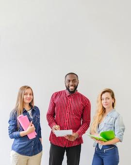 Succesvolle studenten poseren met notitieboekjes