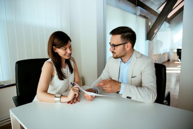 Succesvolle teamwerk, zakelijke man en vrouw zit aan bureau praten over rapporten en financiën
