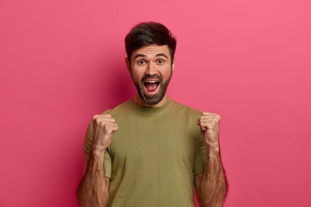 Succesvolle tienerjongen heft gebalde vuisten, viert triomf, kijkt met vreugde, roept luid uit, heeft dikke stoppels, draagt casual t-shirt, poseert over roze muur geschreeuw ja, heeft prijs gewonnen, wint wedstrijd