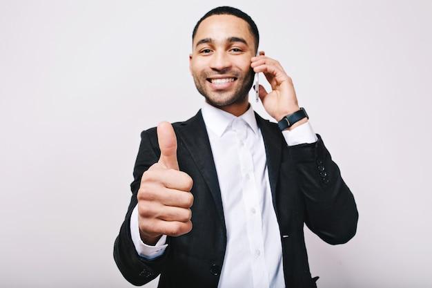 Succesvolle tijd van de jonge knappe man in een wit overhemd, een zwarte jas die positiviteit uitdrukt. telefonisch praten, leiderschap, geweldige carrière, manager, opgewekte sfeer.