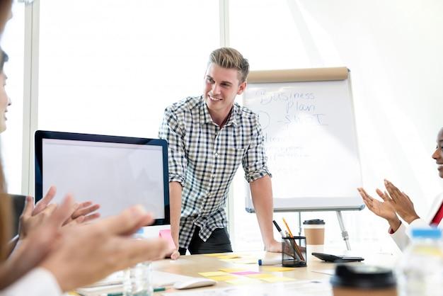 Succesvolle toevallige zakenman die door zijn collega's worden gelukgewenst