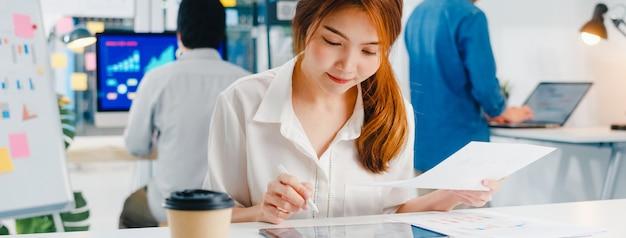 Succesvolle uitvoerende aziatische jonge zakenvrouw slimme vrijetijdskleding tekenen, schrijven en gebruiken van pen met digitale tabletcomputer denken aan inspiratie zoeken ideeën werkproces in modern kantoor aan huis.