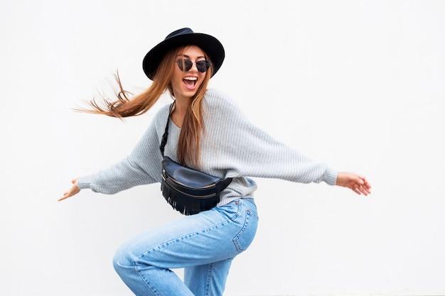 Succesvolle verlaten stijlvolle meisje met openhartige glimlach poseren op witte stedelijke muur