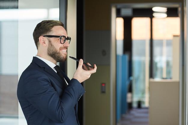 Succesvolle volwassen zakenman in pak heeft een gesprek op de mobiele telefoon terwijl hij buiten staat