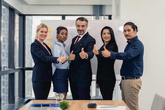 Succesvolle vrolijke bedrijfsmensengroep multiraciaal commercieel team met duimen omhoog en het glimlachen het stellen