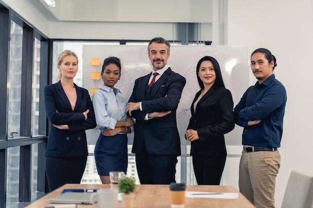 Succesvolle vrolijke zakenmensen groep van multiraciale business team met duimen omhoog en glimlachend poseren