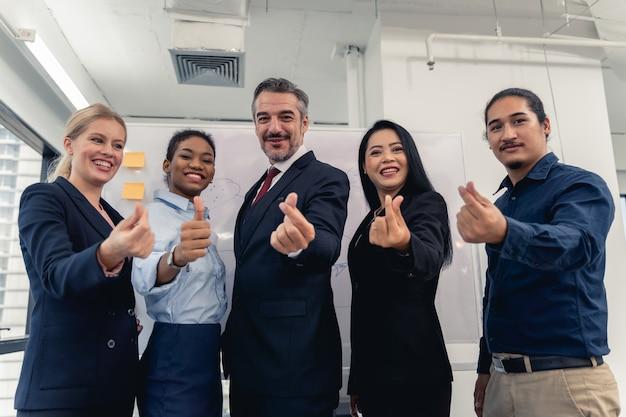 Succesvolle vrolijke zakenmensen groep van multiraciale business team met mini hart en lachend poseren