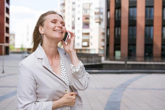 Succesvolle vrouw die aan de telefoon praat en door de straat loopt portret van een stijlvol glimlachend bedrijf...