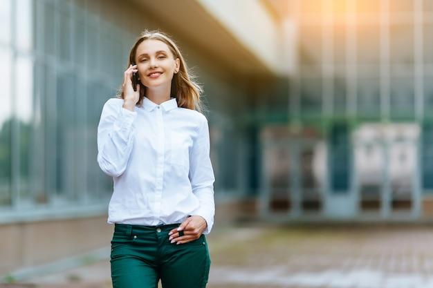 Succesvolle vrouw die buiten in een kantoorgebouw op haar telefoon praat