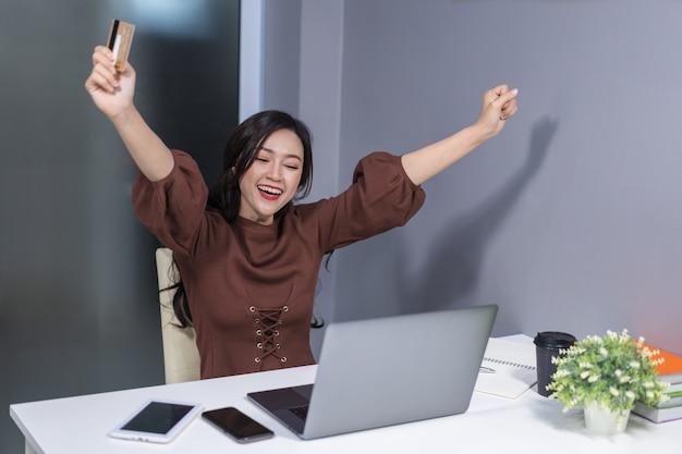 Succesvolle vrouw die laptop computer voor online het winkelen met creditcard met behulp van