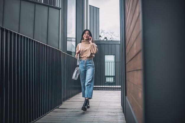 Succesvolle vrouw. vrouw in spijkerbroek en beige blouse lopend en pratend aan de telefoon