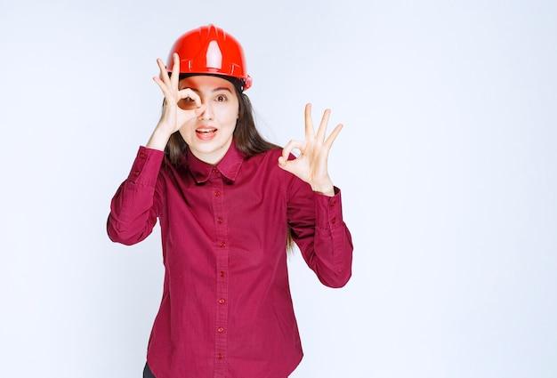 Succesvolle vrouwelijke architect in rode harde helm die ok teken geeft.