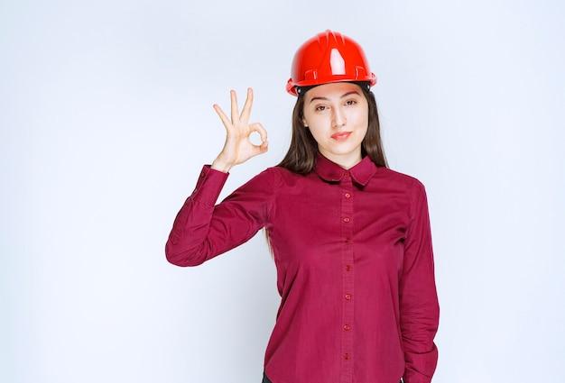 Succesvolle vrouwelijke architect in rode harde helm die staat en een goed teken geeft.