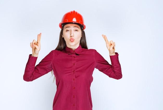 Succesvolle vrouwelijke architect in rode harde helm die staat en tekens geeft.