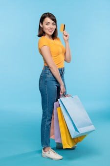 Succesvolle vrouwelijke klant die creditcard toont terwijl ze een stapel boodschappentassen geïsoleerd draagt