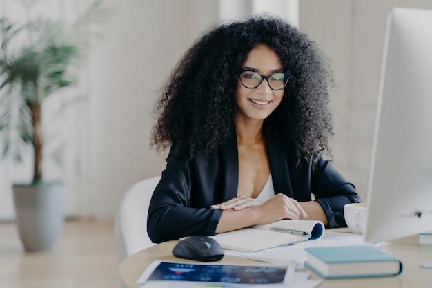 Succesvolle vrouwelijke manager in elegant pak, glimlacht aangenaam, maakt aantekeningen, zit op desktop