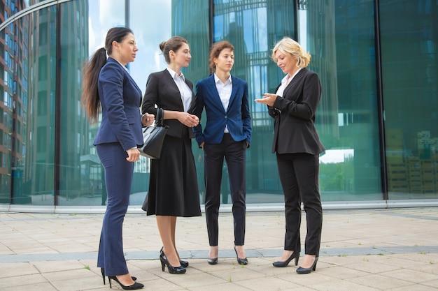 Succesvolle vrouwelijke managers project buiten bespreken. ondernemers dragen pakken, staan samen in de stad en praten. volledige lengte, lage hoek.