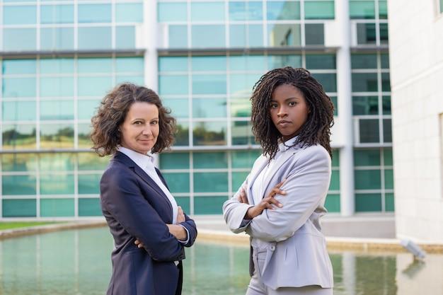 Succesvolle vrouwelijke mix racete zakelijke partners die buiten poseren