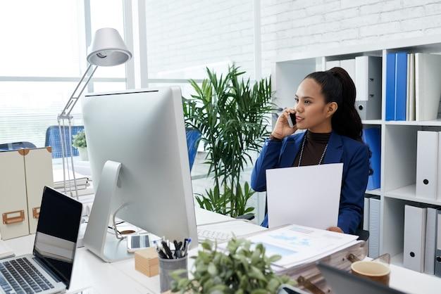 Succesvolle vrouwelijke ondernemer die op kantoor werkt en aan de telefoon praat en nummers bespreekt in wekelijkse r...