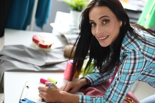 Succesvolle vrouwelijke ontwerper accepteert en schrijft een bestelling van een klant in de werkplaats voor het naaien en repareren van kleding.
