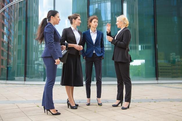 Succesvolle vrouwelijke professionals project buiten bespreken. ondernemers dragen pakken, staan samen in de stad en praten. volledige lengte, lage hoek.