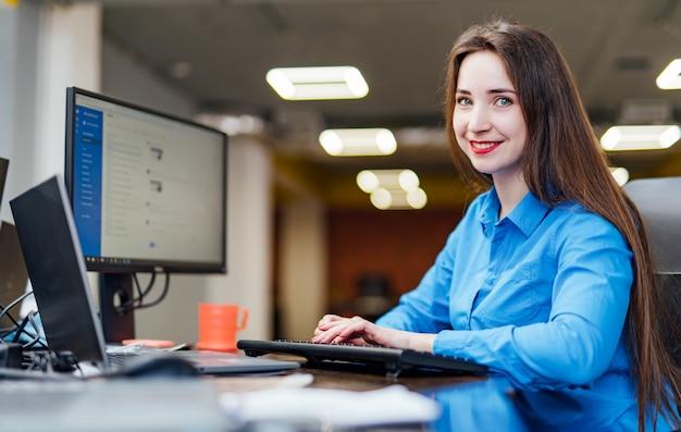 Succesvolle vrouwelijke programmeur zit aan de balie met een computer en werkt. mooie vrouw die vriendschappelijk en in een bureau van het softwarebedrijf glimlacht kijkt.