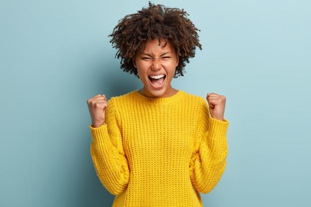 Succesvolle vrouwelijke student met een donkere huid die graag een beurs krijgt, balde vuisten, bereikt doel