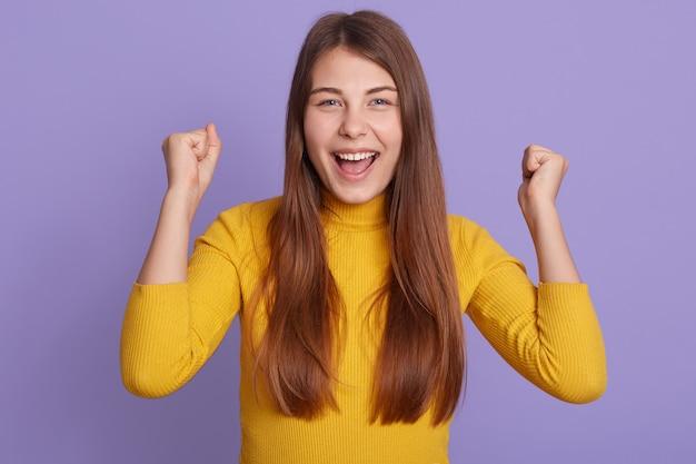 Succesvolle vrouwelijke student ziet er gelukkig uit, balt vuisten, behaalt doel, roept uiteindelijk overwinning uit, staat geamuseerd geïsoleerd over paarse muur.