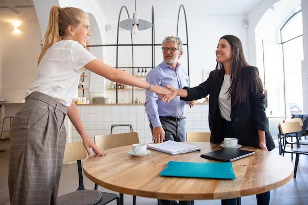 Succesvolle vrouwelijke zakelijke professionele bijeenkomst met klanten en handen schudden