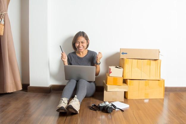 Succesvolle vrouwen in het concept van het online verkoopidee, met werkende laptop computer