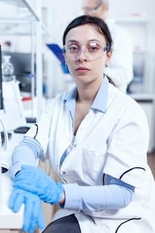Succesvolle wetenschapper in genetica die naar camera kijkt in onderzoekslaboratorium chemicus die laboratoriumjas draagt met behulp van moderne technologie tijdens wetenschappelijk experiment in een steriele omgeving.