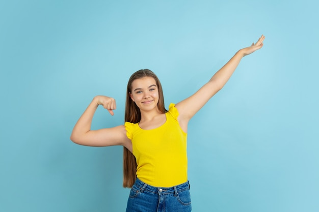 Succesvolle winnaar. het portret van het kaukasische die tienermeisje op blauwe muur wordt geïsoleerd. prachtig model in casual gele slijtage. concept van menselijke emoties, gezichtsuitdrukking, verkoop, advertentie. copyspace. ziet er schattig uit.