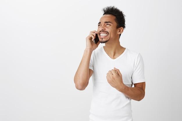 Succesvolle winnende afro-amerikaanse man zegeviert over geweldig nieuws tijdens een telefoongesprek, vuistpomp in de viering